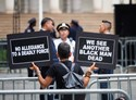 A woman holds signs in front of police officers as she joins a rally at City Hall Park in downtown Manhattan on Aug. 1, 2016. (Anthony DelMundo/New York Daily News)